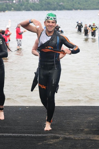Vlad getting out of wetsuit during race with a smile on his face