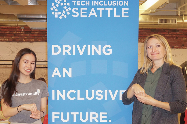"aimee and echo stand in front of tech inclusion banner partially signing ""Incusive"""