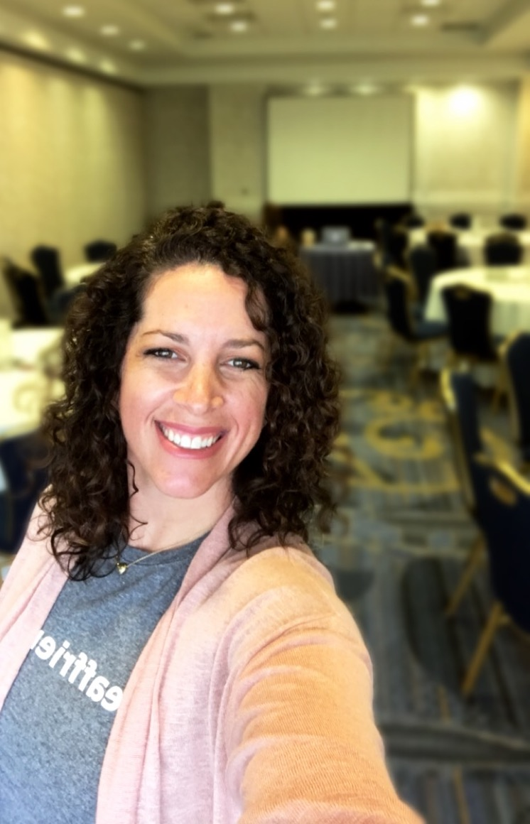 Rachel Berman smiles for the camera in an empty conference room