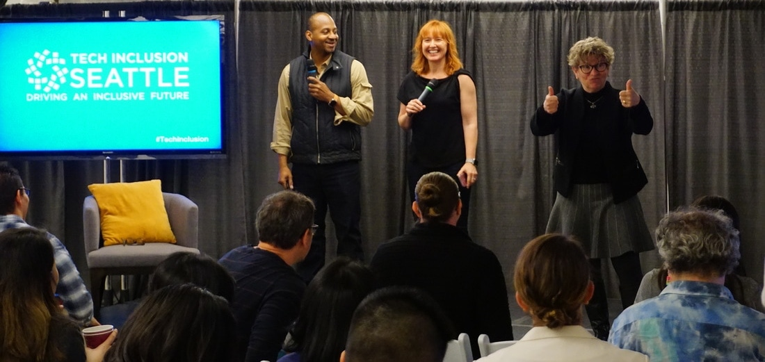 Change Catalyst co-founders Wayne Sutton and Melinda Briana Epler on stage with a sign language interpreter